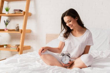 Young woman sitting on bed and looking at retro alarm clock stock vector