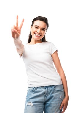 Selective focus of brunette woman in white t-shirt showing peace sign isolated on white stock vector