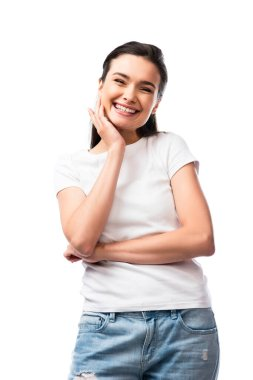 Young brunette woman in white t-shirt touching face and looking at camera isolated on white stock vector