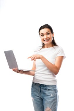 Brunette woman in white t-shirt pointing with finger at laptop laptop isolated on white stock vector