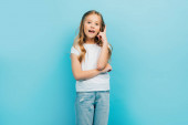 excited girl with open mouth showing idea gesture while looking at camera isolated on blue