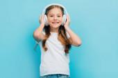 dívka v bílém tričku dotýkající se bezdrátových sluchátek při pohledu na kameru izolované na modré