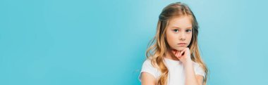 panoramic shot of offended child holding hand near chin while looking at camera isolated on blue