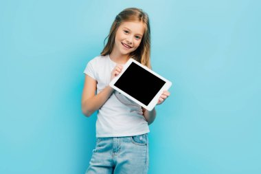 Child in white t-shirt and jeans looking at camera while holding digital tablet with blank screen isolated on blue stock vector