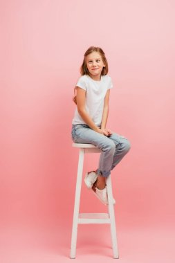 Kid in white t-shirt and jeans grimacing and squinting while sitting on high stool on pink stock vector