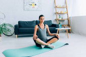 Photo Pregnant woman sitting in yoga pose on fitness mat at home