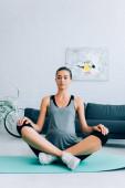 Schwangere Sportlerin sitzt mit gekreuzten Beinen in Yoga-Pose auf Fitnessmatte zu Hause