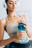 Selective focus of sportswoman listening music in headphones and holding sports bottle at home