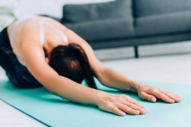 Selective focus of sportswoman stretching after work out on fitness mat at home