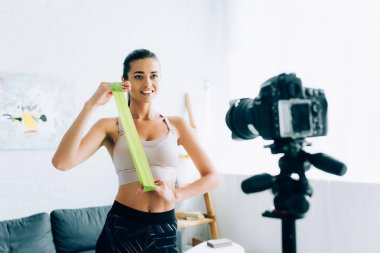 Selective focus of sportswoman holding resistance band near digital camera on tripod at home stock vector