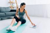 Selektiver Fokus schwangere Sportlerin mit Laptop auf Fitnessmatte zu Hause