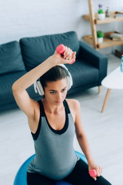Selective focus of pregnant woman in headphones working out with dumbbells and fitness ball in living room
