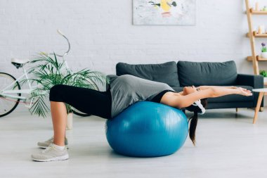 Side view of pregnant sportswoman in headphones training on fitness ball in living room