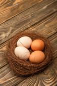 fresh chicken eggs in nest on wooden surface
