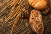 fresh baked bread loaves with spikelets on wooden surface