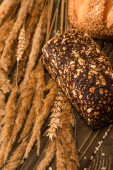 close up view of fresh baked bread loaves with spikelets on wooden surface