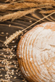 selective focus of fresh baked bread loaf with spikelets on wooden surface