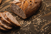 cut fresh baked bread with seeds on wooden surface