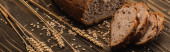 cut fresh baked bread with spikelets on wooden surface, panoramic shot