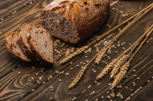 cut fresh baked bread with spikelets on wooden surface