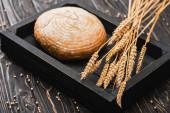 čerstvý pečený bílý bochník chleba s hřeby na dřevěné černé desce