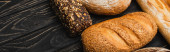 fresh baked bread loaves on wooden black surface, panoramic shot