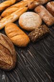 čerstvé pečené bochníky chleba na dřevěném černém povrchu