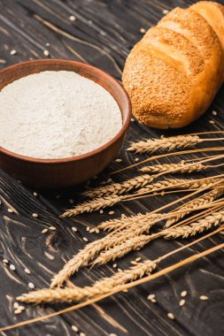 fresh baked white bread loaf with wheat flour in bowl and spikes on wooden surface