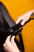 ostříhaný pohled na kadeřníka pomocí rovnání vlasů a hřeben izolované na žluté
