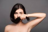 nahý bruneta žena drží vlasy v blízkosti obličeje izolované na černé