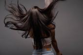 Rückseite der brünetten langhaarigen Frau isoliert auf schwarz