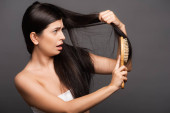 shocked brunette woman brushing hair isolated on black