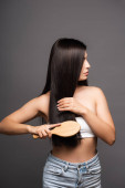 Photo cropped view of brunette woman brushing shiny hair isolated on black