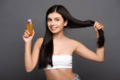 Photo brunette woman holding hair and oil in bottle isolated on black