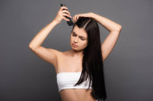 Photo sad brunette long haired woman shaving head with electric razor isolated on black