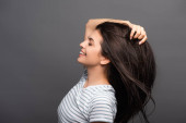 Photo side view of brunette woman with closed eyes smiling and touching hair isolated on black