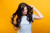 brunette woman toughing curly long hair and smiling isolated on yellow
