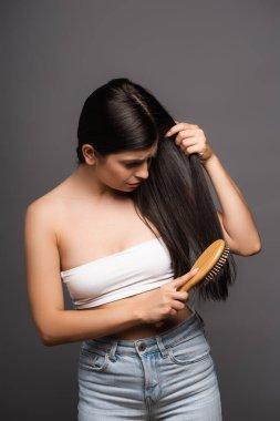 Worried brunette woman brushing hair isolated on black stock vector