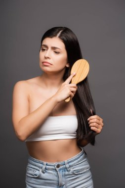 Sad brunette woman brushing hair isolated on black stock vector