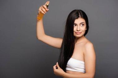 Brunette woman spraying oil on hair isolated on black stock vector