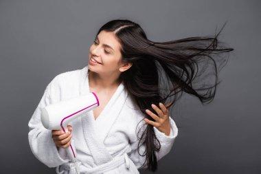 Brunette long haired woman in bathrobe using hairdryer isolated on black stock vector