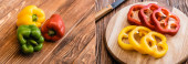 collage of colorful ripe whole and sliced bell peppers on wooden table, panoramic shot