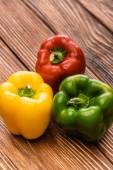 barevné zralé papriky na dřevěném stole