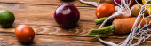 Photo fresh ripe vegetables scattered from string bag on wooden table, panoramic shot