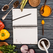 top view of fresh colorful vegetables and spices near blank notebook on wooden surface