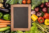 Blick von oben auf frisches buntes Gemüse um leere Tafel