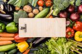 vrchní pohled na čerstvou barevnou zeleninu kolem prázdné dřevěné schránky