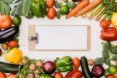 vrchní pohled na čerstvou zralou zeleninu a ovoce v blízkosti prázdné schránky na dřevěném bílém pozadí