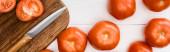 shora pohled na zralá rajčata na sekací desce s nožem na bílém dřevěném stole, panoramatický záběr