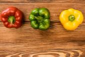 vrchní pohled na barevné zralé papriky na dřevěném stole